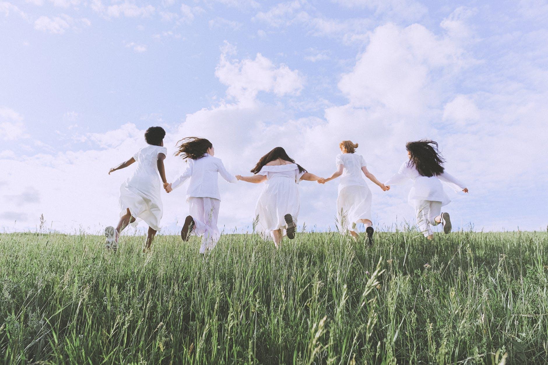 group of women running on green grass field